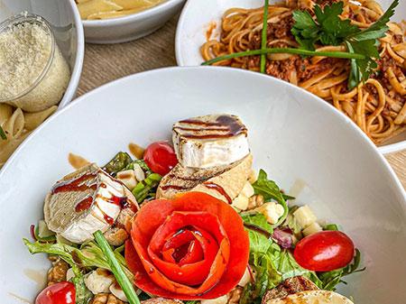 Salade de chèvre, tomates et croutons, et plat de pâtes.